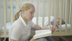 An adult woman reads a book sitting next to a sleeping little baby in a baby crib stock video footage