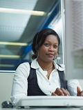 Adult woman working in call center. Female african american customer service representative talking on the phone and typing on pc. Vertical shape, front view Royalty Free Stock Photo