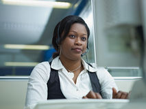 Adult woman working in call center. Female african american customer service representative talking on the phone and typing on pc. Horizontal shape, front view Royalty Free Stock Images