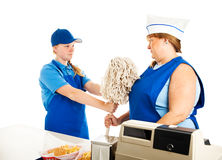 Adult Woman Works for Teenage Boss. Teenage fast food manager makes an adult women mop up.  white background Royalty Free Stock Photos