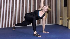 An adult woman in yoga makes a warrior pose in the studio. On a blue surface adult sports lady in a black elastic suit and special shoes makes a complex stock video footage