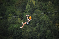 Adult woman on zip line. Adult beautiful woman on zip line royalty free stock image