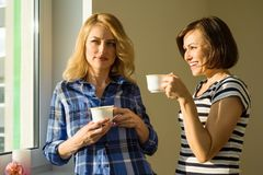Adult women drink coffee, talk, laugh. Royalty Free Stock Photos