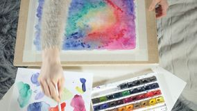Adult women paint with colored watercolor paints in an art school close up