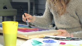 Adult women paint with colored watercolor paints in an art school close up. 4k
