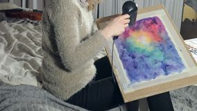 Adult women paint with colored watercolor paints and dry with a hair dryer in an art school stock video footage