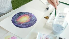 Adult women paint with colored watercolor paints in an home studio close up. 4k