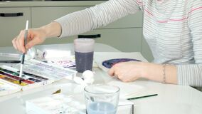 Adult women paint with colored watercolor paints in an home studio. 4k