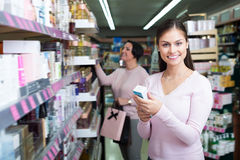 Adult women picking cream from shelf Royalty Free Stock Photography