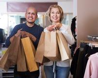 Woman purchasing stylish clothes. Adult women purchasing stylish clothes in the shop Royalty Free Stock Photo