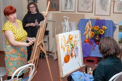 Adult women students sit at easels, studying painting royalty free stock photography