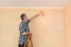 Adult worker paint wall in a room to orange Royalty Free Stock Image