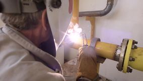 Adult worker is welding two gas pipes with manual welding machine, repairing old worn-out gas equipment. View from his back stock footage