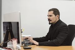 Adult 35 years old worker in office at computer royalty free stock image
