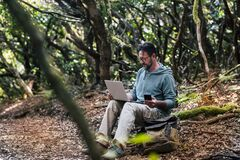 Free Adult Young Man Work With Online Roaming Connection Technology Outdoor With Phone And Laptop Computer - People In Nature Outdoors Stock Photography - 203016352