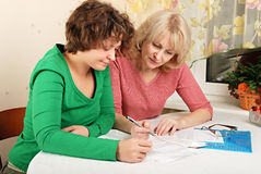 Adult and young women with documents Stock Images