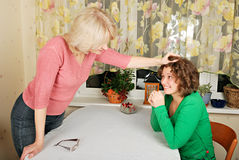 Adult and young women: jocular punishment. Adult blond woman and young woman jocular punishment Stock Photo