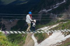 Adulte et enfant sur un pont de corde dans les montagnes photos libres de droits