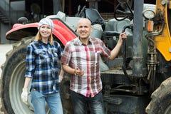 Adulte et jeunes exploitants agricoles travaillant aux machines Image libre de droits