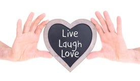 Adulte tenant le tableau en forme de coeur - vivent l'amour de rire Photographie stock