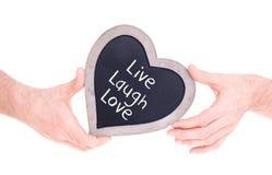 Adulte tenant le tableau en forme de coeur - vivent l'amour de rire Photographie stock libre de droits