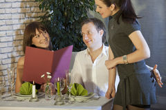 Adultery in restaurant. Man holding his hand on waitress buttocks in a restaurant Stock Image
