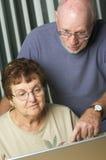 Adultes aînés sur l'ordinateur portable Photographie stock