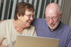 Adultes aînés sur l'ordinateur portable Photos stock