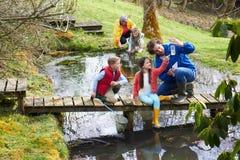Adultes avec des enfants sur le pont au centre d'activité en plein air Images libres de droits