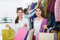 Adultes dans la bonne humeur tenant des sacs au magasin d'habillement Photos stock