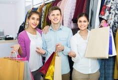 Adultes dans la bonne humeur tenant des sacs au magasin d'habillement Image libre de droits