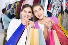 Adultes dans la bonne humeur tenant des sacs au magasin d'habillement Photographie stock
