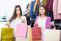 Adultes dans la bonne humeur tenant des sacs au magasin d'habillement Images libres de droits