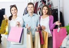 Adultes dans la bonne humeur tenant des sacs au magasin d'habillement Images stock