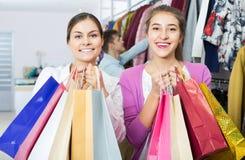 Adultes dans la bonne humeur tenant des sacs au magasin d'habillement Photo stock