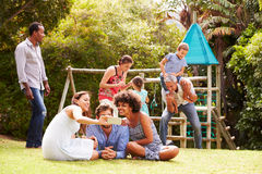 Adultes et enfants ayant l'amusement dans un jardin Photographie stock