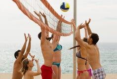 Adultes jetant la boule au-dessus du filet et de rire Photographie stock