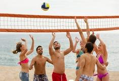 Adultes jetant la boule au-dessus du filet et de rire Images stock