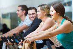 Adultes montant les bicyclettes stationnaires dans le centre de fitness Image stock
