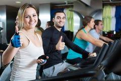 Adultes montant les bicyclettes stationnaires dans le centre de fitness Images libres de droits
