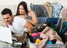 Adultes s'asseyant près de l'ordinateur portable et du bagage Image libre de droits