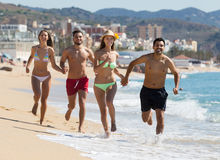 Adulti che corrono alla spiaggia sabbiosa Immagine Stock