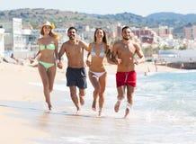 Adulti che corrono alla spiaggia sabbiosa Fotografia Stock
