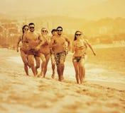 Adulti felici che corrono alla spiaggia sabbiosa Fotografia Stock