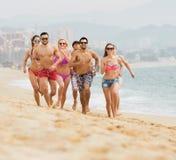 Adulti felici che corrono alla spiaggia sabbiosa Immagine Stock