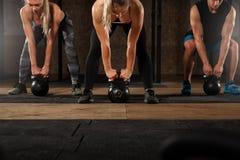 Adulti muscolari che si esercitano con la campana del bollitore in palestra Fotografie Stock Libere da Diritti