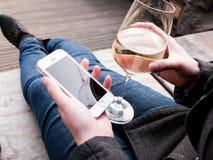 Adulto al aire libre usando un teléfono y una consumición elegantes Fotografía de archivo