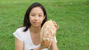 Adulto asiático de la mujer que come los carbohidratos del pan Imagen de archivo