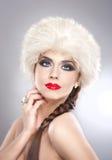 Adulto caucásico joven atractivo aislado en fondo gris. Muchacha hermosa con los labios rojos en el sombrero de piel blanco - estu Imagenes de archivo