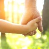 Adulto che tiene la mano di un bambino, mani del primo piano Fotografia Stock